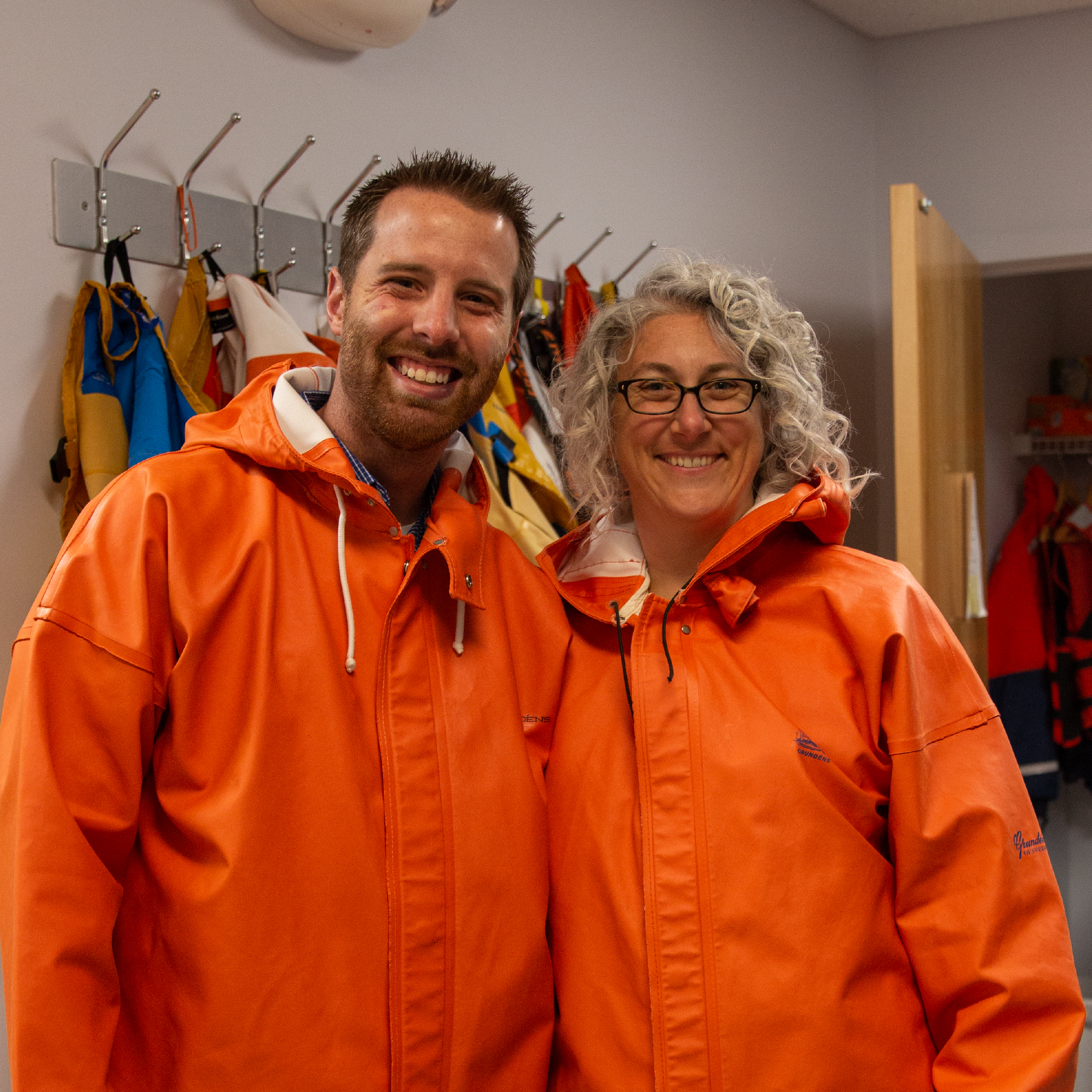 Breeding Insight team members don protective clothing as they prepare to enter a salmon breeding facility.